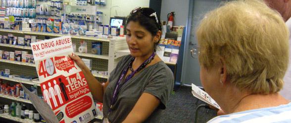 Diana Plazas entregando afiches y las bolsas en las farmacias participantes en los condados de Gwinnett y DeKalb.