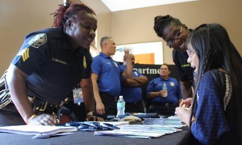 Una niña latina habla con una de las oficiales de la policía de Atlanta.