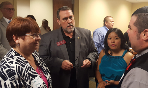 Durante la apertura, la comisionada de Gwinnett Charlotte J. Nash, el representante Pedro Marín y la virtual representante Brenda López, mientras saludan a algunos asistentes.